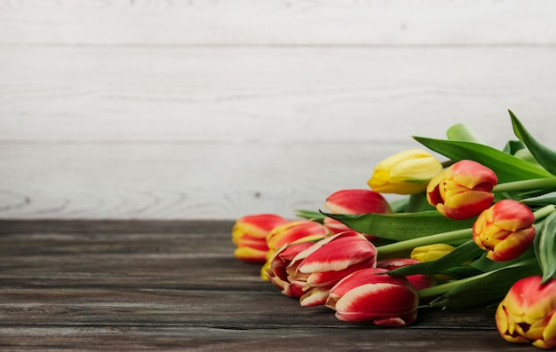 白い木製の背景コピースペースに赤、黄色、ピンクのチューリップの花束。古い木製のテーブルのチューリップ。