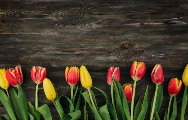 茶色の木製の背景に赤、黄色、ピンクのチューリップコピースペース。古い木製のテーブルフラットにチューリップを置きます。