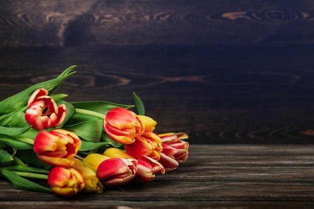 茶色の木製の背景コピースペースに赤、黄色、ピンクのチューリップの花束。古い木製のテーブルのチューリップ。