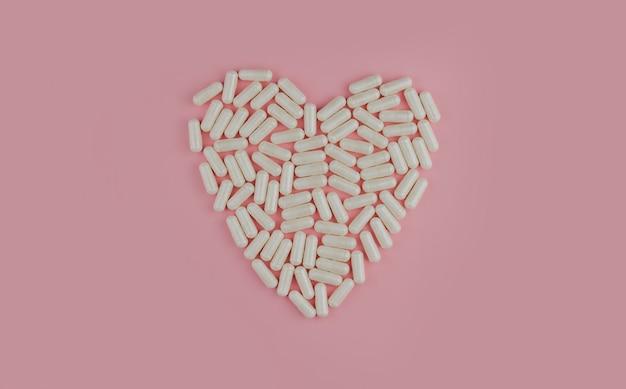 Белые таблетки на розовой стене. разбросанные таблетки. сердце из таблеток.