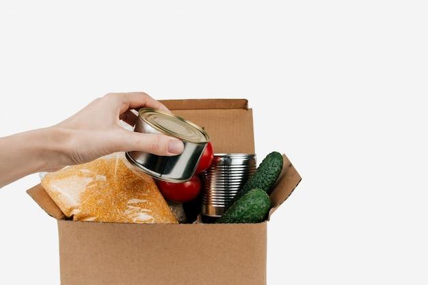 Коробка с продуктами. овощи, крупы и консервы в картонной коробке изолированы. консервная банка в руке.