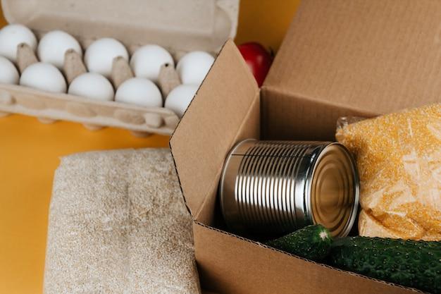 Продукты для пожертвований на желтом фоне. овощи, крупы и консервы. еда пожертвования копировать пространство.