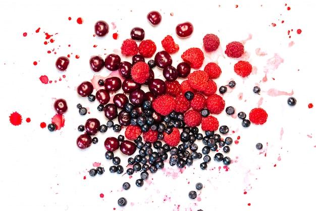 ブルーベリー、ラズベリー、白のジュースの滴とチェリー
