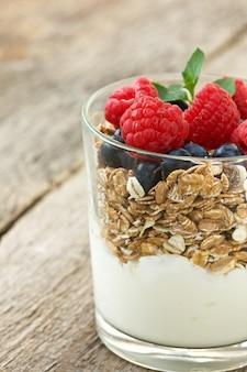 Мюсли и йогурт со свежими ягодами в стеклянной банке