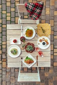 Завтрак подается в кафе стол с сырными блинами, бутербродом, круассаном и напитками. вид сверху