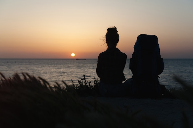 夕日を背景にバックパックを持つ少女のシルエット