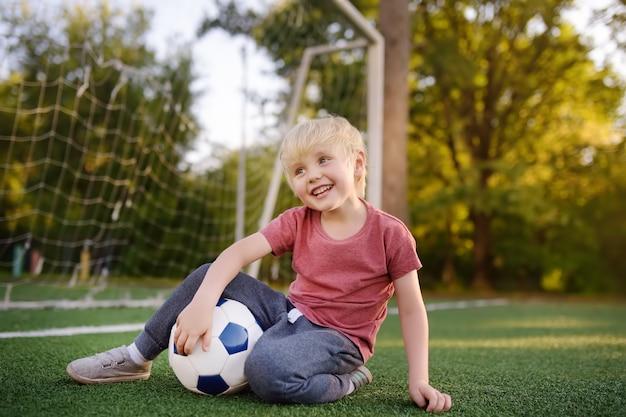 楽しんで夏の日にサッカー/フットボールの試合を楽しんでいる少年。