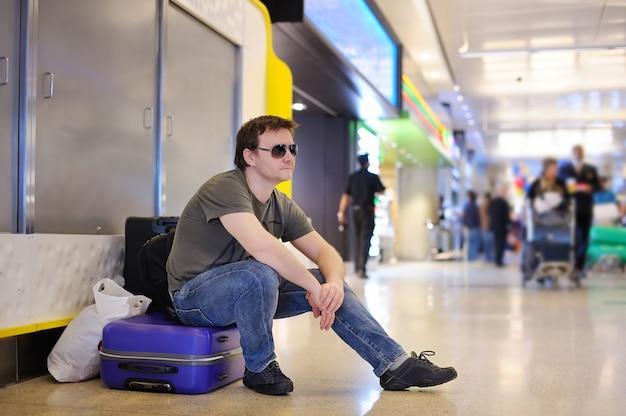 Уставший пассажир мужского пола в аэропорту сидит на чемоданах