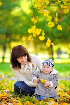 秋の公園で楽しんでいる彼女の小さな男の子を持つ若い母親