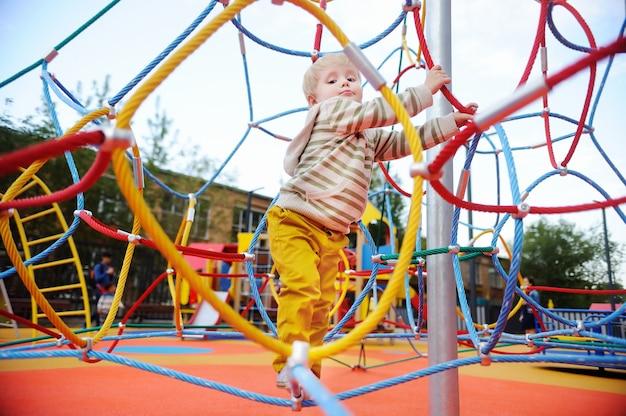 遊び場で楽しんでかわいい幼児男の子。小さな子供向けのアクティブアウトドアゲーム