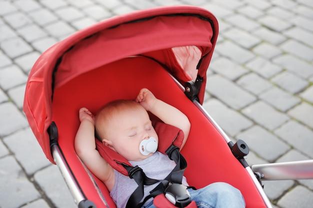 Милый маленький мальчик спит в коляске