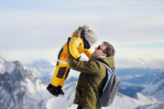 冬のドイツのツークスピッツェへの旅行中に彼の父の腕の中で小さな男の子。