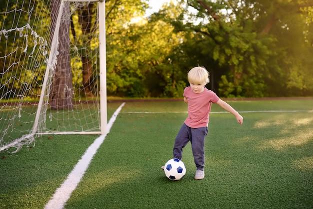 Маленький мальчик, с удовольствием играют в футбол / футбол на летний день.