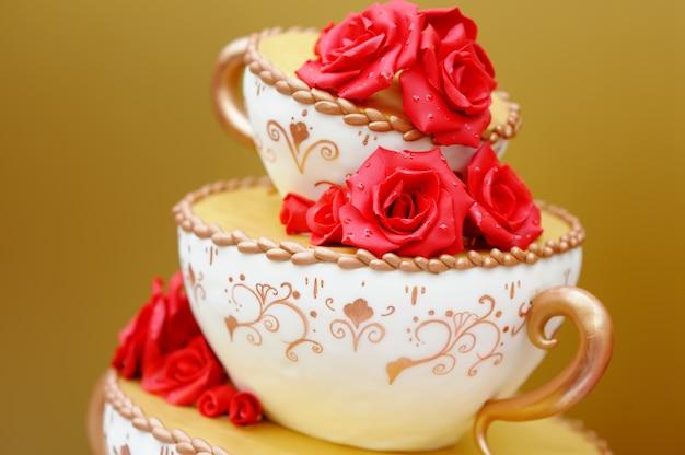 赤い花で飾られたおいしいオリジナルのウェディングケーキ