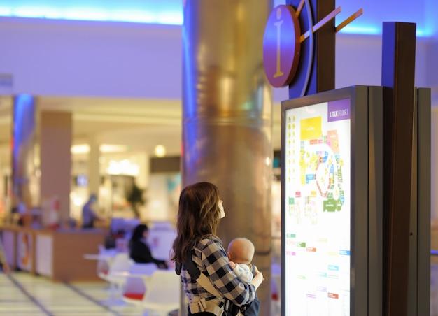 ショッピングモールで彼女の小さな赤ちゃんを持つ若い女