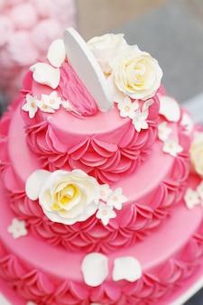 白いクリーム色のバラで飾られたおいしいピンクのウェディングケーキ
