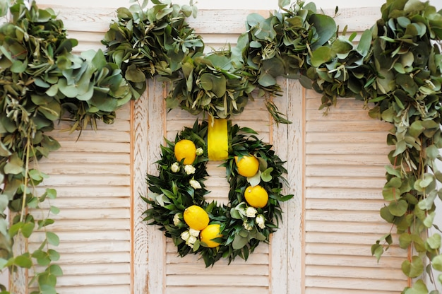 Венок из лавровых листьев, роз и лимонов в качестве украшения на дереве