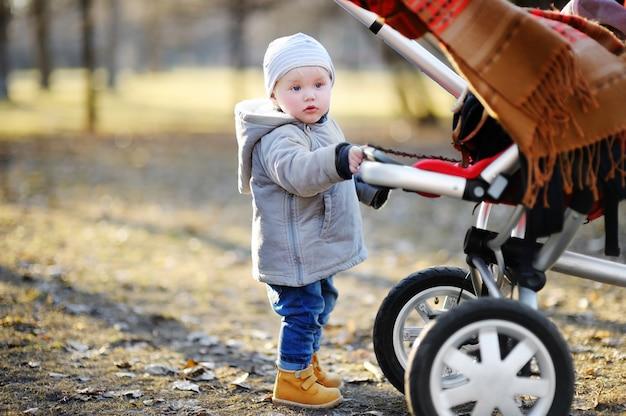 暖かい春の日に野外を歩いている彼のベビーカーと遊ぶ美しい幼児男の子