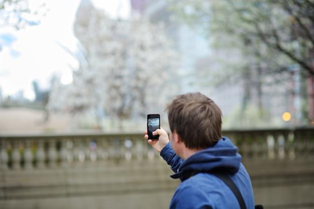 彼のスマートフォンを使用してモバイル写真を撮る中年男性の観光客
