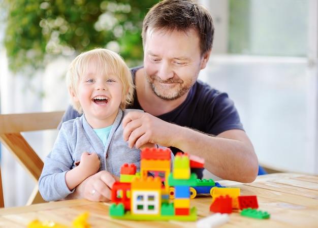 Маленький мальчик со своим отцом, играя с красочными пластиковых блоков у себя дома