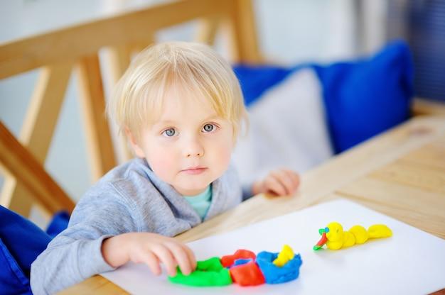 Творческий мальчик играет с красочными лепка из глины в детском саду
