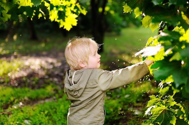 雨の後の夏の公園で楽しんでかわいい幸せの小さな男の子の肖像画