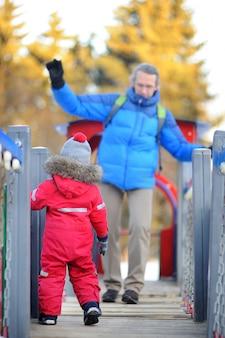 雪に覆われた冬の公園で一緒に楽しんで彼の父/祖父と小さな男の子