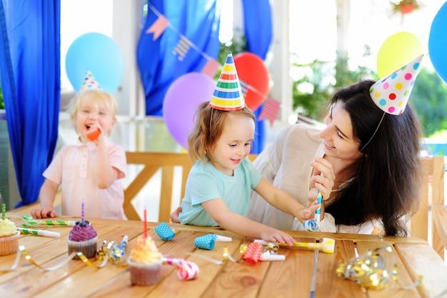 小さな子供とその母親は、カラフルな装飾とケーキでカラフルな装飾とケーキで誕生日パーティーを祝う