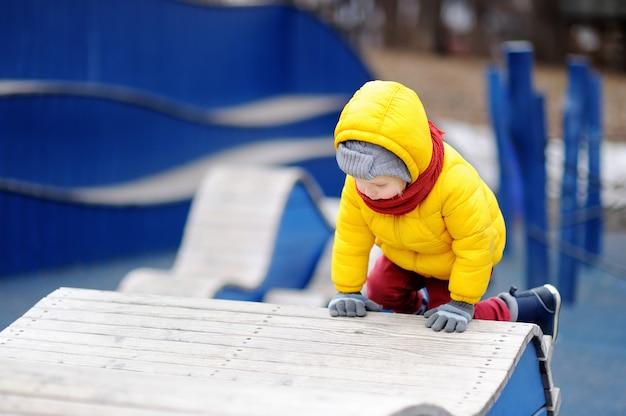 屋外の遊び場で楽しんでかわいい男の子