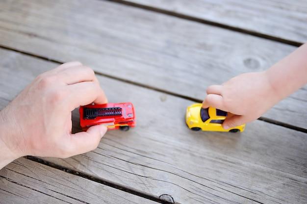 おもちゃの車で遊ぶ彼の幼い息子を持つ父