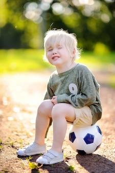 夏の日のサッカー/フットボールの試合中に秋の後泣いている男の子