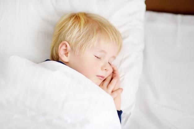 Милый маленький мальчик спит. усталый ребенок вздремнуть в постели родителей.