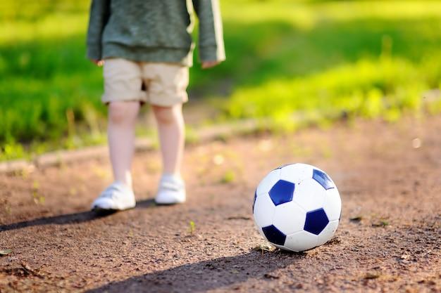 Маленький мальчик с удовольствием играет в футбол / футбол в летний день