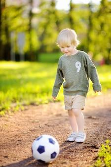 Маленький мальчик с удовольствием играет в футбол в солнечный летний день