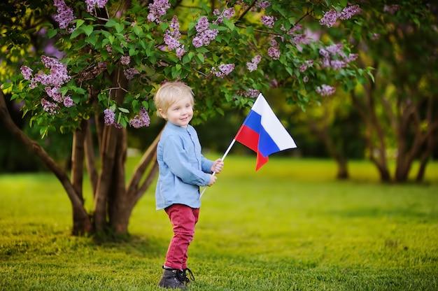 ロシアの国旗を保持しているかわいい男の子。ロシアの子供たち。選挙や国民の祝日の概念。ロシア連邦
