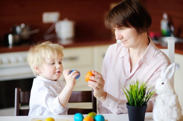 Красивая женщина и ее милый сын или внук, играя с пасхальное яйцо на пасху