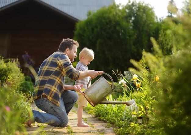 中年の男と彼の幼い息子は夏の晴れた日に庭の花に水をまく