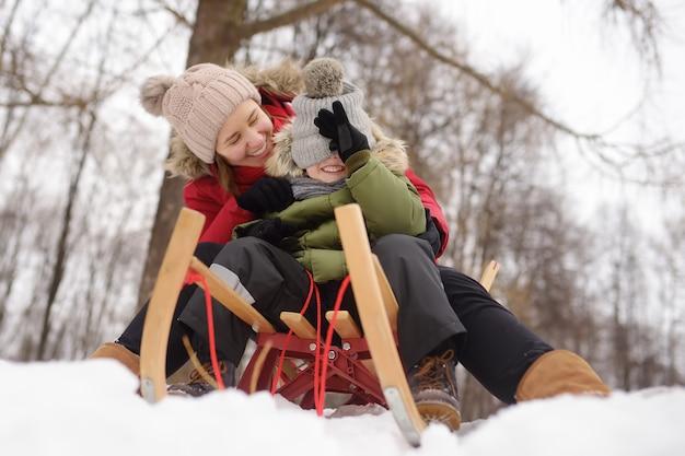小さな男の子と母親は、雪の滑り台での滑りを楽しんでいます。