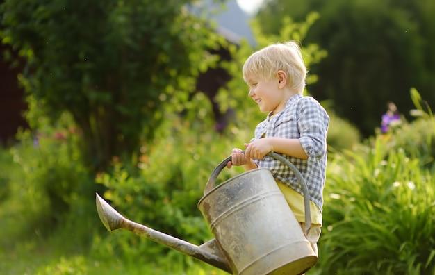 夏の晴れた日に庭の植物に水をまくかわいい幼児少年。
