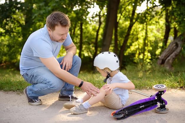 スクーターに乗ることを学習中に安全ヘルメットの小さな男の子が落ちます。クラッシュ後の息子を慰める父。子供との安全、スポーツ、レジャー
