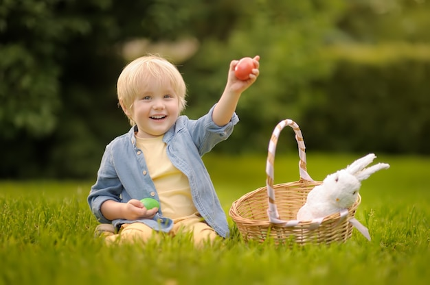Очаровательная охота мальчика на парк пасхального яйца весной на день пасхи.