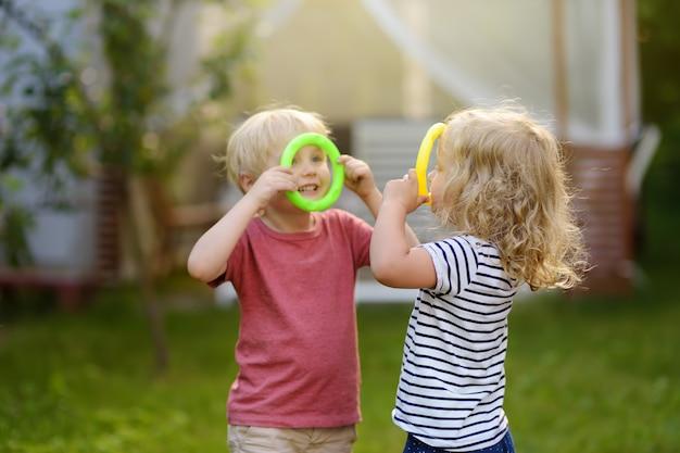 かわいい男の子と女の子の夏の屋外でリングを投げるゲームで遊ぶ