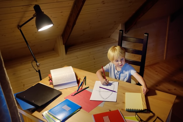 Маленький мальчик делает домашнее задание, рисует и пишет дома вечером