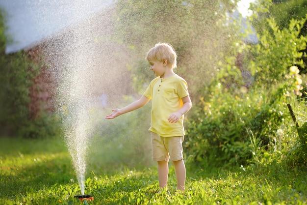 Забавный маленький мальчик, играя с садовым разбрызгивателем в солнечном дворе
