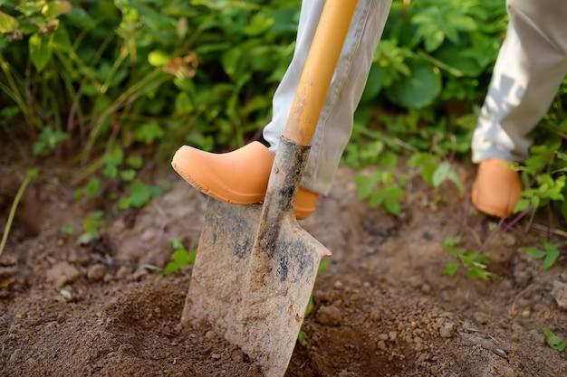 Женщина копает лопатой в своем дворе.