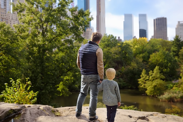 Мужчина и ее очаровательный маленький сын восхищаются видами в центральном парке
