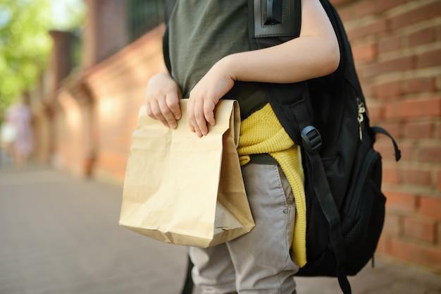 Студент с большим рюкзаком и сумкой с обедом возле здания школы.