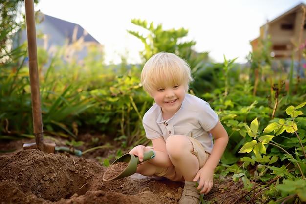 夏の晴れた日に裏庭でシャベルで掘る小さな男の子。