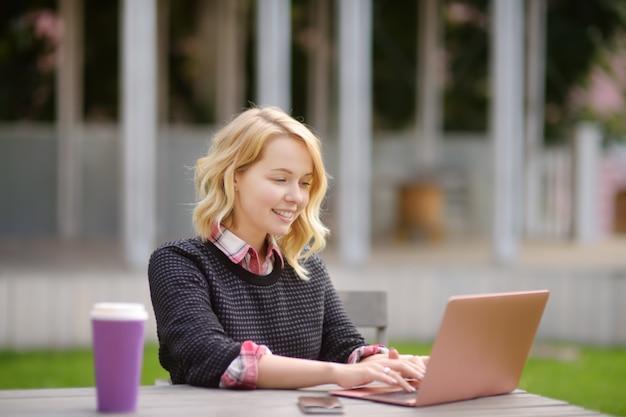 若い女性の勉強/作業と美しい一日を楽しんで