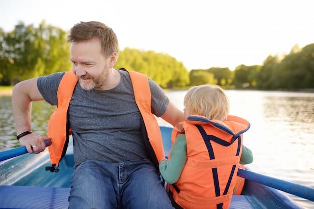 成熟した父と晴れた夏の日に川や池でボートの幼い息子。